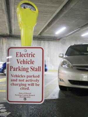 An electric vehicle charging station awaits a vehicle in the parking lot at the Hawaii State Legislature on Wednesday, Jan. 18, 2017 in Honolulu. Renewable energy advocates in Hawaii are pushing a bill to urge the transportation sector to get all its energy from renewable sources in 2045.