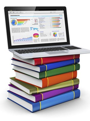 Laptop on stack of color books