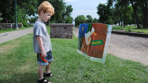 """Miles Kendig, 4, of Sioux Falls, looks at a page from the book, """"One Duck Stuck,"""" during the fourth annual Siouxland Library Book Walk on Wednesday, July 22, 2015, along the bike path between downtown Sioux Falls and Falls Park. Children and adults walked along the bike path stopping to read pages from children's books along the way."""