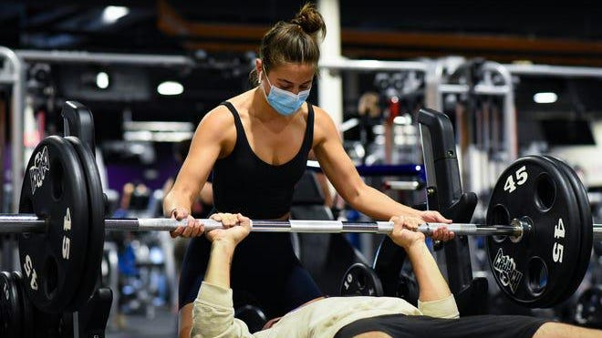 Melinda Wander of East Lansing spots husband Zach, Saturday, Sept. 26, 2020, during a workout at Crunch Fitness in East Lansing. The newlyweds worked out in their backyard when gyms were closed.