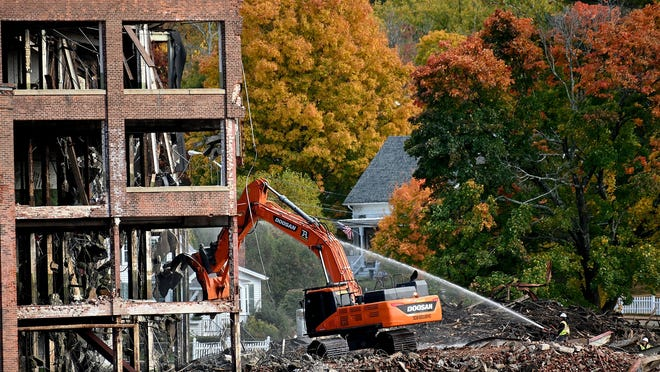Fall foliage create a colorful background as an excavator demolishes a section of the the Draper factory, a downtown Hopedale landmark for most of the 20th century, on Wednesday, Oct. 21.