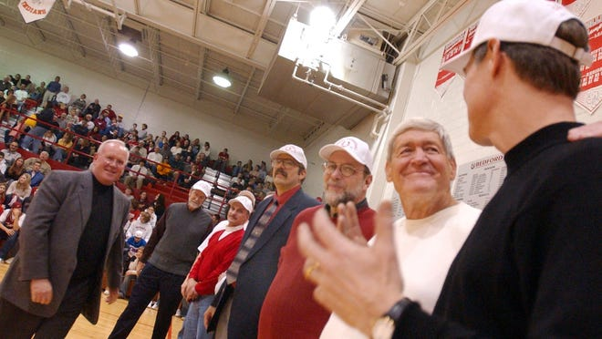 Gary Duhaime (in white shirt) is honored with the 1969-70 Bedford boys basketball team during halftime of a game in 2004.
