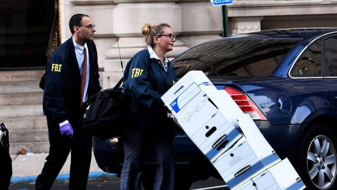 FBI agents leave the Paterson City Hall annex with boxes of documents late Thursday, Nov. 3, 2016.