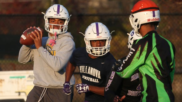 From left, New Rochelle quarterback Jonathan Saddler looks for an open receiver during football practice at New Rochelle High School Nov. 16, 2016. New Rochelle will  play Troy in the state semifinal this Saturday in Kingston.