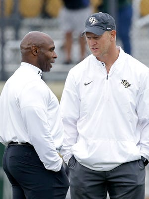 University of Central Florida coach Scott Frost, right, is being pursued by his alma mater, Nebraska, for their vacant football coaching position.