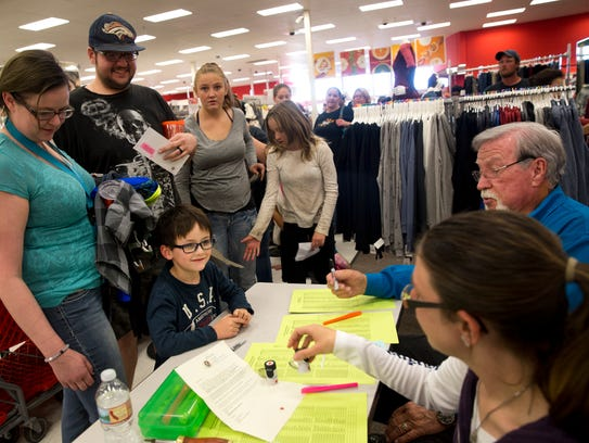 Shelby Liu, left, and Joseph Blackwood check in their son Link Liu Thursday during the Rio del Sol Kiwanis Club's Clothes for Kids event at Target in Farmington.