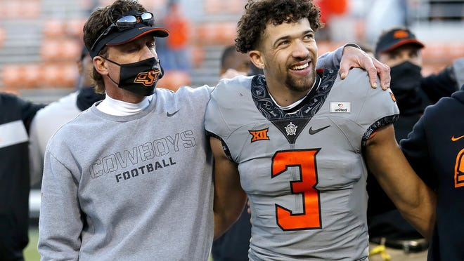 Oklahoma State head coach Mike Gundy sings the alma mater with quarterback Spencer Sanders after beating Iowa State 24-21 last week at Boone Pickens Stadium. The sixth-ranked Cowboys host Texas this week.