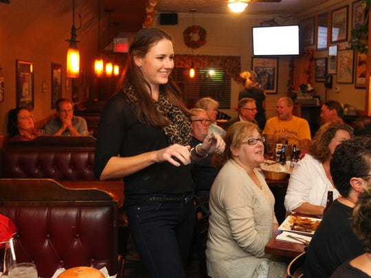 """Pro golfer Tessa Teachman shares a laugh with family and friends during a watch party at the Fairport Village Inn. Teachman is a contestant on the Golf Channel's """"Big Break Myrtle Beach."""""""