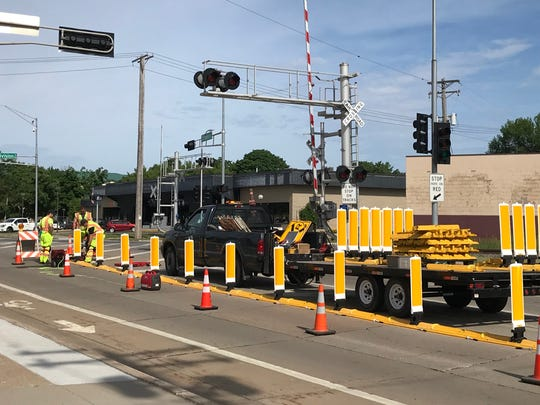 Workers install barriers at the intersection of Franklin