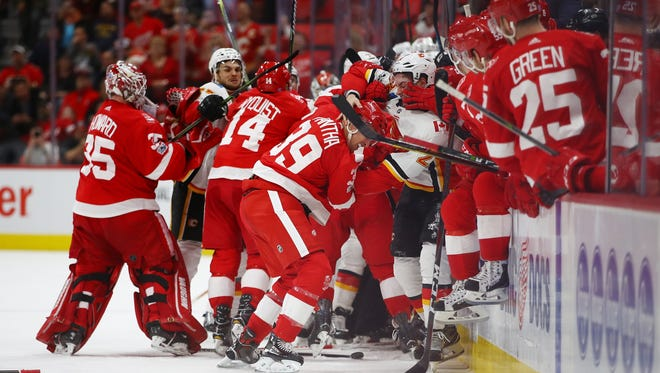 A fight breaks out by the benches between the Calgary Flames and Detroit Red Wings at Little Caesars Arena on November 15, 2017 in Detroit, Michigan. Detroit won the game 8-2.