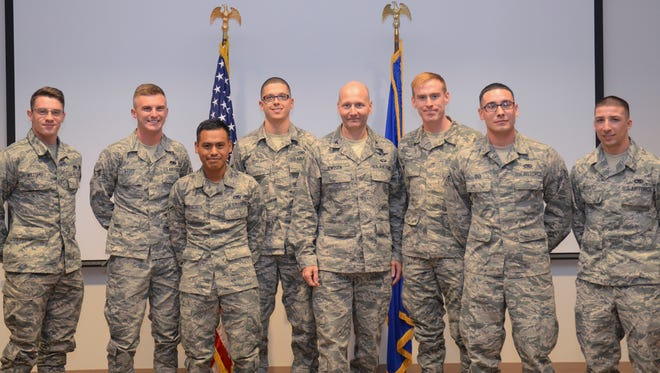 Colonel Jeffrey Jenssen, the 54th Fighter Group commander, center, poses for a picture with class 16-006 of the Sole Hands-On Training Mission Ready Airmen F-16 training course after receiving their certificates of completion at Holloman Air Force Base on Dec. 16. This is the first graduation of its kind to be held at Holloman. The course originally started at Luke Air Force Base, Arizona, until it was transferred here about a month ago.