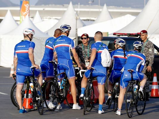 d6483920c Athletes of the France cycling team talk with Brazilian security forces as  they arrive at the