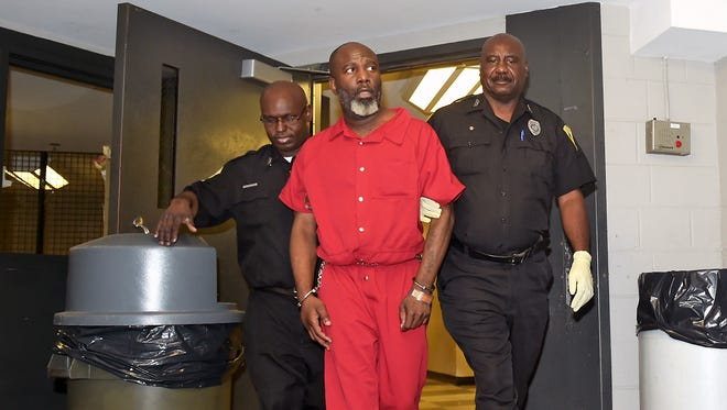 Devell Bingham, 39, is escorted from the Jackson Police Department after his initial court appearance Wednesday. Bingham is being charged with two counts of murder for Tuesday's shooting deaths of Bingham's mother and step-father.