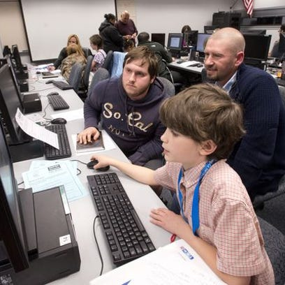 Young entrepreneur Ian Robertson, front, works with Web designer James Harrington and mentor Chris Thom, right, to develop his product during a recent Young Entrepreneurs Academy meeting at UWF.