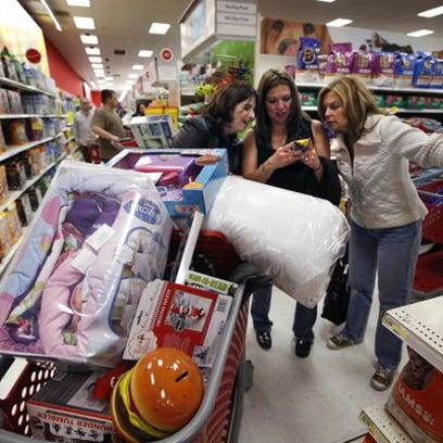 In this Nov. 28, 2014, file photo, Target shoppers Kelly Foley, left, Debbie Winslow, center, and Ann Rich use a smartphone to look at a competitor's prices while shopping shortly after midnight on Black Friday, in South Portland, Maine.