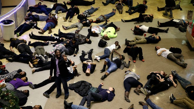 "Protesters stage a ""die in"" at Chesterfield Mall in Chesterfield, Mo., as part of protests of a grand jury's decision not to indict police officer Darren Wilson in the shooting death of Michael Brown in nearby Ferguson, Mo."