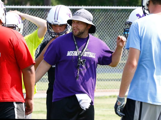Mosinee new head coach Craig Martens, middle, works with the high school's football team during Tuesday's practice at Mosinee High School football field.