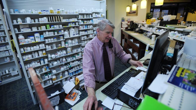 Tommy Rayfield fills prescriptions while he answers the phone at Rayfield's Pharmacy in Nassawadox, Va., on Wednesday, April 8, 2015. The business is celebrating its 40th anniversary this month.