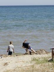 People enjoy the vista of Lake Michigan at Kohler-Andrae