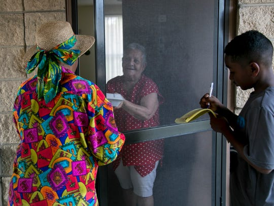 Carmen Gonzalez, center, accepts a meal Sophie Mae Lewis and her grandson Ahmir Miller on Saturday, December 17, 2016. The pair delivered nearly 90 meals to low-income residents of Palm City Gardens and Ohio Place.