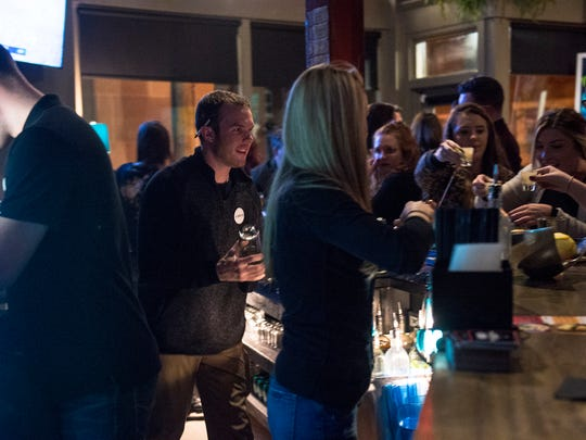 """Bartenders, including Johnny Hyman, left of center, serve patrons during a monthly Guerrilla Gay Bar event Saturday, March 10, 2018, at Crystal Ball Brewing Co. in York. Crystal Ball hired an additional bartender in anticipation of increased volume Saturday. Every second Saturday, the Guerrilla Gay Bar group chooses a bar in York to """"take over"""" as a pop-up event to create a space for York's LBTQ community to socialize and explore different parts of the city's bar scene."""