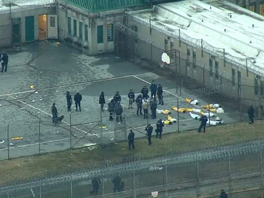 Inmates are contained in the Smyrna prison yard after Building C was secured earlier this morning.