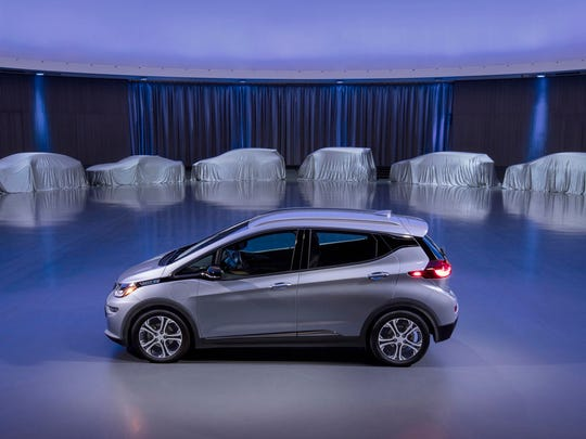 A Chevrolet Bolt is surrounded by nine electric and fuel cell vehicles covered by tarps. On Monday, Oct. 2, 2017, GM announced the company will produce two new electric vehicles on the Bolt underpinnings in the next 18 months and 20 electric and hydrogen fuel cell vehicles by 2023.