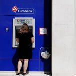 A customer enters a Eurobank branch while another uses an automated teller machine in Athens on  July 20, 2015.