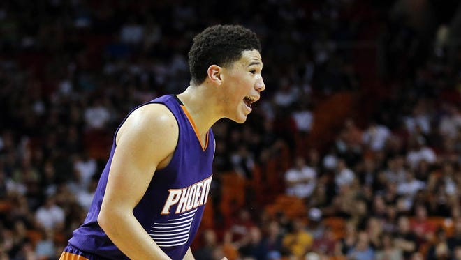 Mar 3, 2016: Phoenix Suns guard Devin Booker (1) reacts after drawing a foul against Miami Heat guard Dwyane Wade (not pictured) during the second half at American Airlines Arena. The Heat 108-92.