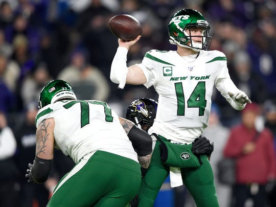 New York Jets quarterback Sam Darnold (14) throws a pass as Baltimore Ravens defensive end Jihad Ward, center, grabs at him during the first half of an NFL football game, Thursday, Dec. 12, 2019, in Baltimore. (AP Photo/Gail Burton)