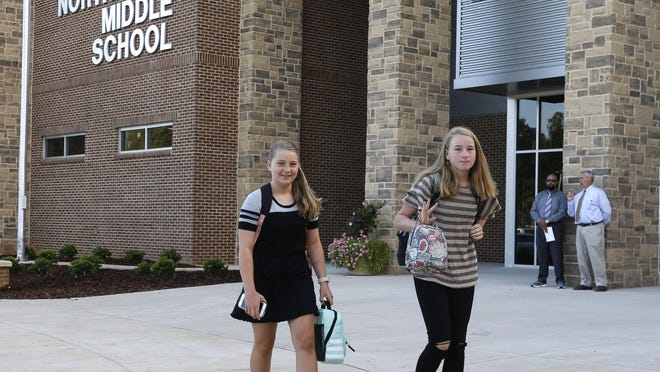 Isabella Benz and Laura Bushhorn walk in front of the new Northridge Middle School as they come for the first day of school Wednesday August 8, 2018.