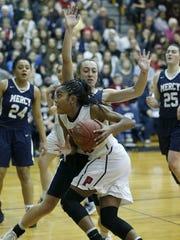 Penfield's Makaila Wilson runs around Mercy's Leah
