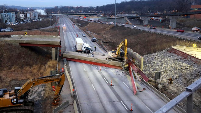 Work continues in the aftermath of the bridge collapse on Interstate 75, Tuesday, Jan. 20, 2015 in Cincinnati. The collapse killed a worker and injured a truck driver.