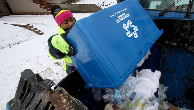 Nicole Henry of Flint adds more recyclable materials including many empty water bottles into a large container on a Republic Services recycling truck in Flint on Wednesday.