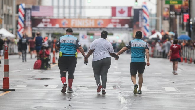 Walkers make their way to the finish line during the 39th Detroit Free Press/Talmer Bank Marathon in Detroit on Sunday.