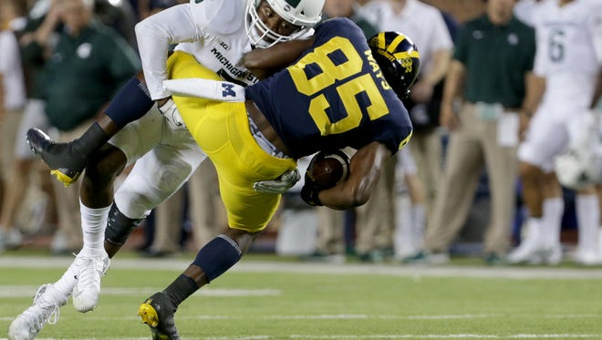 Michigan State's Andrew Dowell tackles Michigan's Maurice Ways after he caught a pass in the first half at Michigan Stadium in Ann Arbor on Saturday, October 7, 2017.