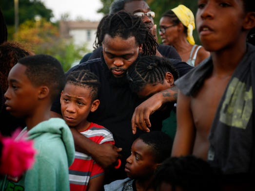 Lovell Logan holds his family during a vigil to morn