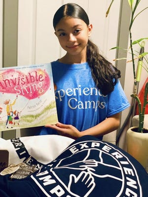 A camper shows off swag unpackged from an Experience Camp 'Camp-in-a-box'.