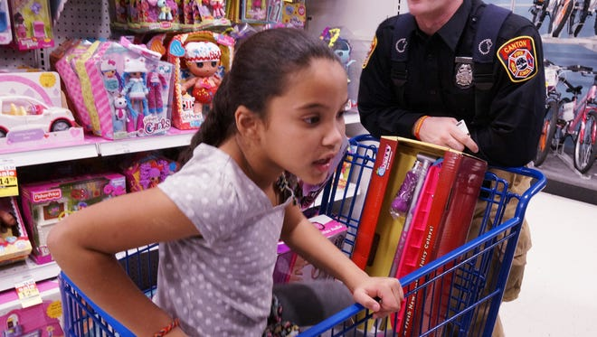 Firefighter Michael Thoms helps a child pick out Christmas gifts during a charity program by Canton firefighters.