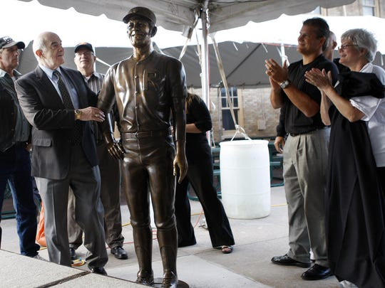Joe Altobelli, second from left, surrounded by family, gets his first glimpse at the new statue at Frontier Field honoring him in September 2010.