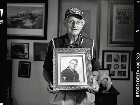 In this file photo, Lonnie Cook poses with a portrait of himself during his time in World War II.