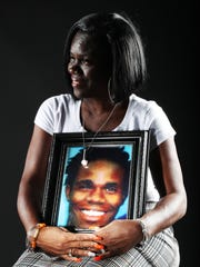 Camelia Schley poses with a photo of her murdered son