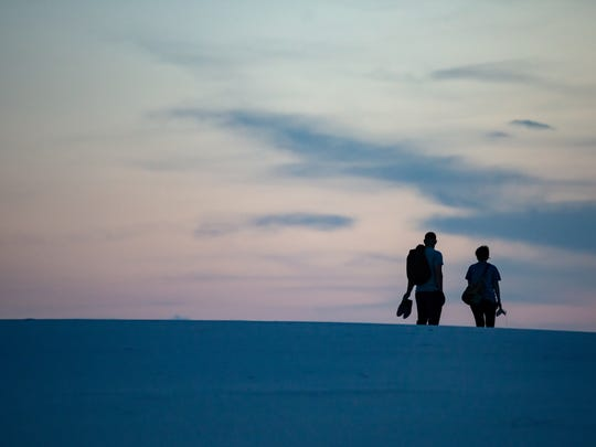 A couple walks the sand dunes as the sun sets on Friday Jul7 27, 2018 for Full Moon Nights at White Sands National Monument.