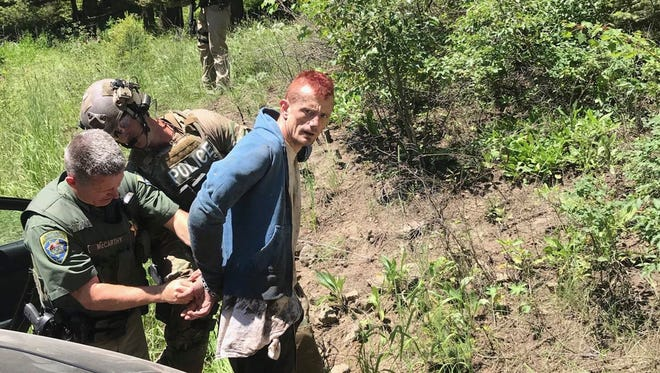 In this Thursday. July 12, 2018 photo provided by the Park County Sheriff's Office, officers arrest 36-year-old Shaunesy Cole in the Bozeman Pass area after he fled pursuing officers in Bozeman, Mont. Cole suspected of shooting at law enforcement officers during a pursuit in southern Montana was arrested on a warrant charging him with attempted deliberate homicide. (Park County Sheriff's Office via AP)