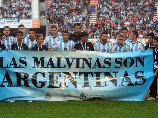 """Argentina's team poses for a picture with a banner reading in Spanish """"The Malvinas are Argentine"""" referring to the Malvinas Islands or the Falkland Islands before an international friendly soccer match against  Slovenia in La Plata, Argentina, Saturday, June 7, 2014.(AP Photo/Raul Ferrari- Telam)"""