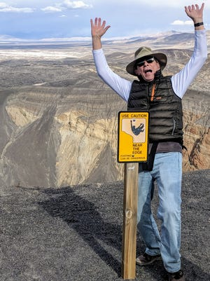 Having a photo taken, as columnist David Loe did, mimicking the caution sign overlooking Death Valley's 600-foot deep Ubehebe Crater is a badge of courage for those surviving the hike around its rim. (credit: Darrell McMahon)
