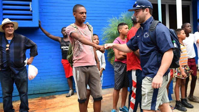 Penn State outfielder James Coates is greeted by Cuban youth outside the Estadio Latinoamerica before the team's game against the Industriales in Havana, Cuba on Monday. The Industriales beat the Nittany Lions, 2-1.
