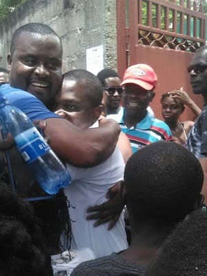 Estimable Francius Dauphin is hugged by a joyous supporter after being released from jail.