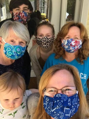 Medway's Sharon Hebert, front, and members of her family model some of the face masks they have been making in memory of her daughter, Helen, 15. Clockwise from front: Sharon Hebert, Rycker Hebert, 13 months, of Bellingham; Sharon McGrath of Medway, Walter Hebert, 19; Arianna Hebert, 20, of Bellingham, and Kerrie Hebert, of Bellingham.