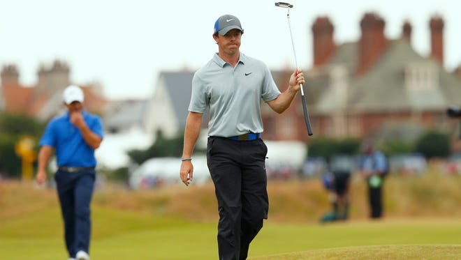 Rory McIlroy of Northern Ireland acknowledges the crowd as he walks to the 18th green during the third round of the British Open Championship at the Royal Liverpool Golf Club in Hoylake, northern England July 19, 2014.